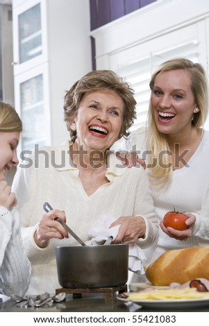 Three generation family in kitchen serving lunch, talking and laughing - stock photo
