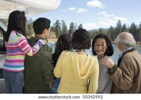 Three-generation family looking at lake, back view - stock photo