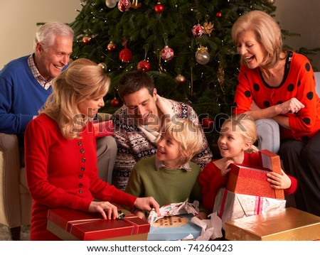 Three Generation Family Opening Christmas Gifts At Home - stock photo