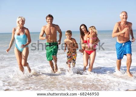 Three generation family play on beach - stock photo