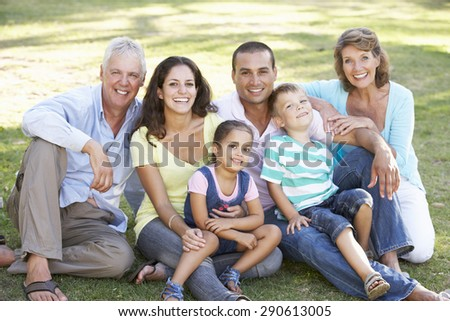 Three Generation Family Relaxing In Summer Park