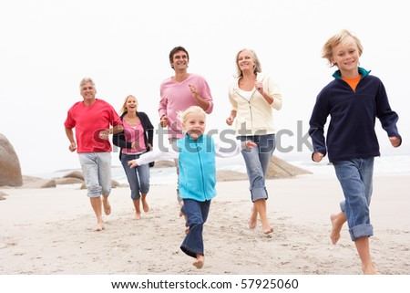 Three Generation Family Running Along Winter Beach Together - stock photo