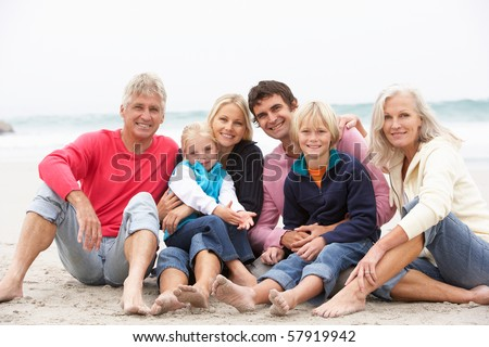 Three Generation Family Sitting On Winter Beach Together - stock photo