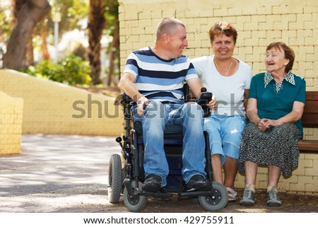 Three generation family sitting together in the park  - stock photo