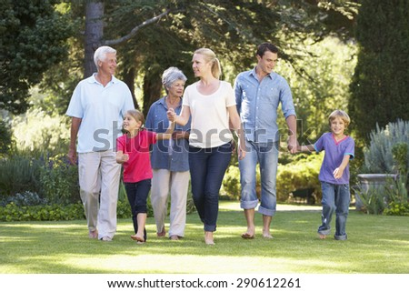 Three Generation Family Walking In Garden Together - stock photo