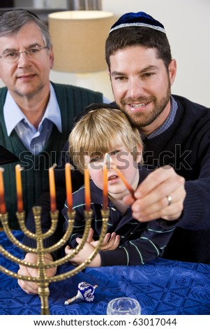 Three generation Jewish family lighting Chanukah menorah - stock photo