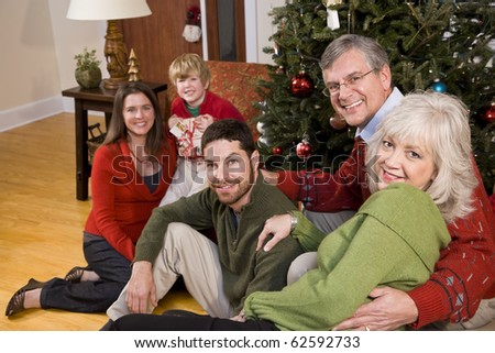 Three generations - family holiday gathering by Christmas tree - stock photo