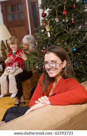 Three generations - happy mother at Christmas with boy and grandmother in background - stock photo