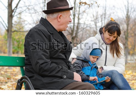 Three generations of a family at the park with an elderly grandfather sitting on a wooden bench with his daughter and grandson