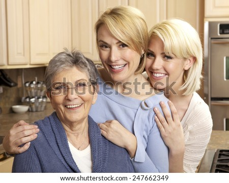 Three generations of beautiful women smiling in a kitchen - stock photo