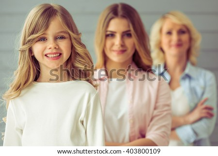 Three generations of family are looking at camera and smiling, standing one by one. Pretty little girl in the foreground