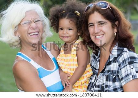 Three generations of hispanic women including a small child - stock photo