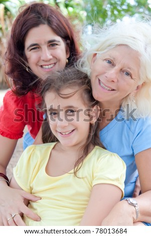 Three generations of latin women hugging and sitting in a park - stock photo
