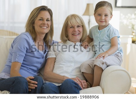 Three generations sitting on couch - stock photo