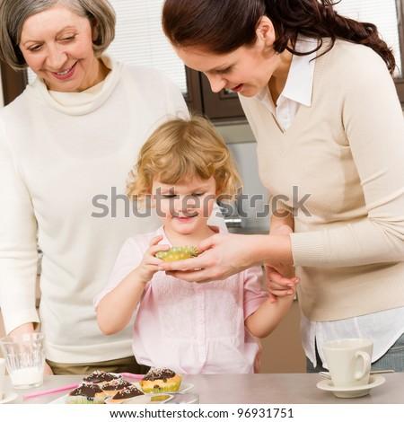 Three generations women around cupcake little girl tasting cookies - stock photo