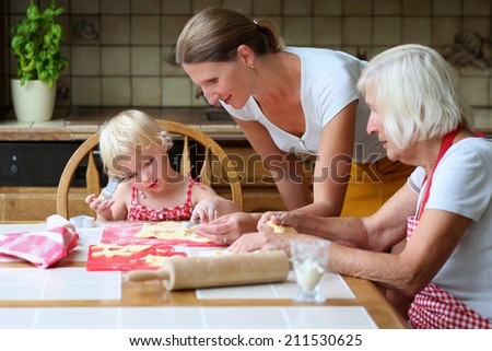 Three generations: young woman baking tasty sweet cookies together with her daughter, cute little toddler girl, and mother, loving caring senior woman, sitting at the table in classic wooden kitchen - stock photo