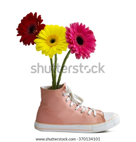 Three gerbera flowers are in a vase made out of old shoes - stock photo