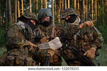 Three german soldiers discuss a plan of action. Coordinate the team. - stock photo