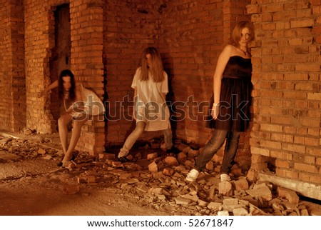 Three ghosts of young girls in abandoned building - stock photo