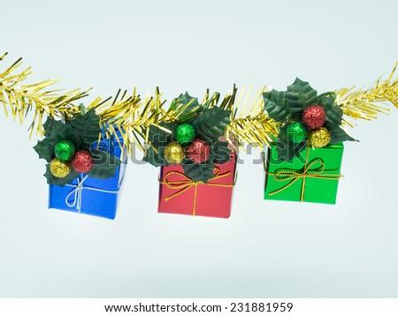 Three gift box hang on golden garland - stock photo