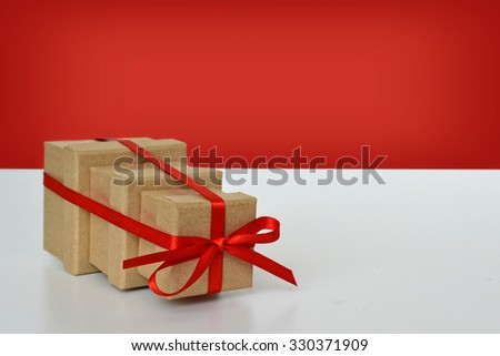 Three gift boxes tied together with red ribbon
