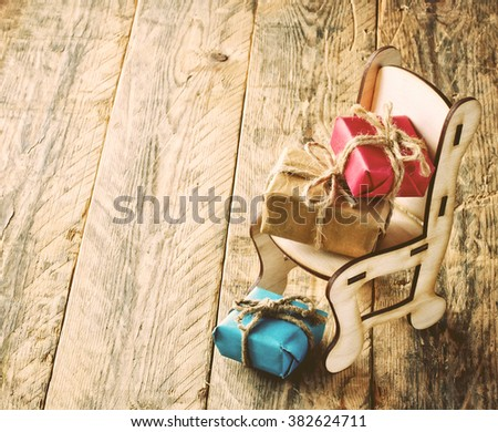 three gift boxes, toy chair on old wooden table, retro style - stock photo