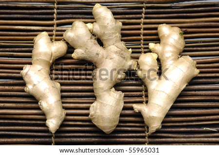 Three ginger root on bamboo mat - stock photo