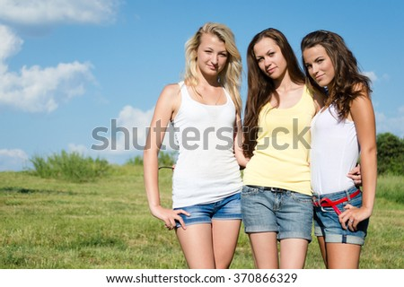 Three girl friends in jeans shorts over blue sky  - stock photo