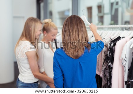 Three Girl Friends Looking at the Clothes Hanging on Rail Inside a Clothing Store - stock photo