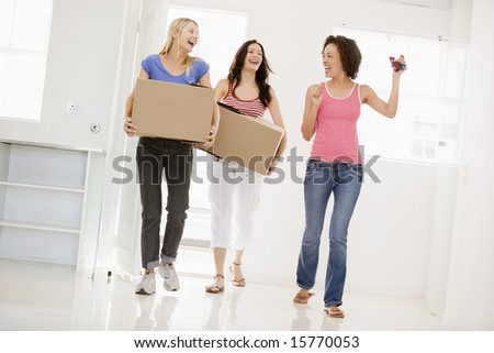 Three girl friends moving into new home smiling - stock photo
