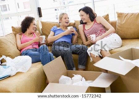 Three girl friends relaxing with coffee by boxes in new home smiling - stock photo