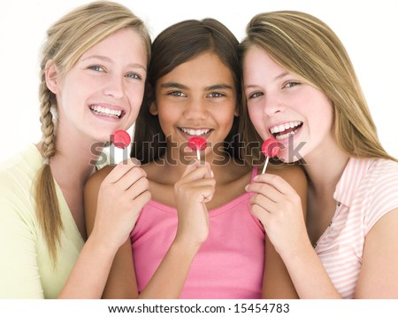 Three girl friends with suckers smiling - stock photo