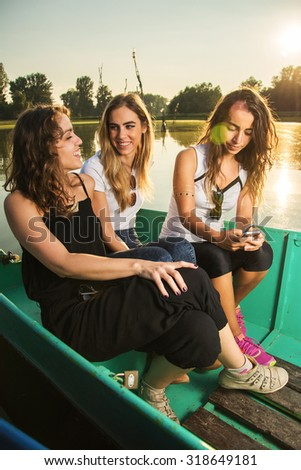 Three girlfriends enjoying spare time on boat near the river at sunset. - stock photo
