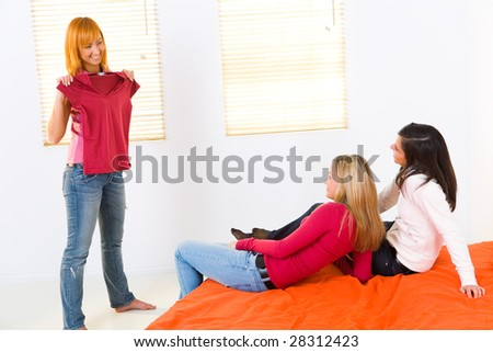 Three girlfriends in room. One of them showing new T-shirt. Two girls  lying on bed. - stock photo
