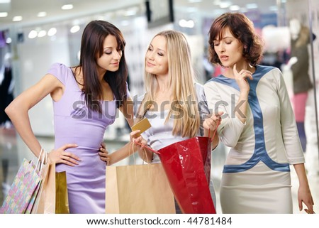 Three girlfriends in shop with bags and a credit card - stock photo