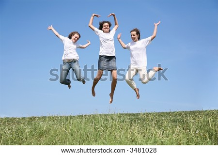Three girlfriends in white T-shorts jump simultaneously