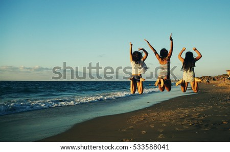 Three girlfriends jumping on the beach at sunset