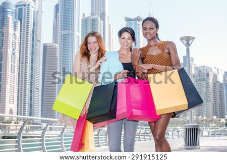Three girlfriends shopaholic. Beautiful girl in dress holding shopping bags in their hands on the promenade facing the camera while shopping bags - stock photo