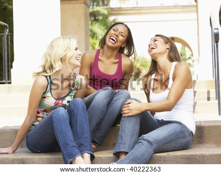 Three Girlfriends Sitting On Steps Of Building