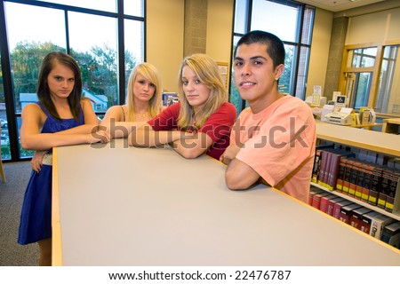 Three girls and one boy standing at school with their arms folded and frowning. Horizontally framed photo. - stock photo