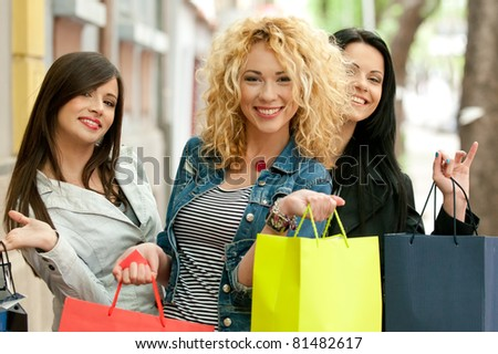 Three girls back from shopping - stock photo