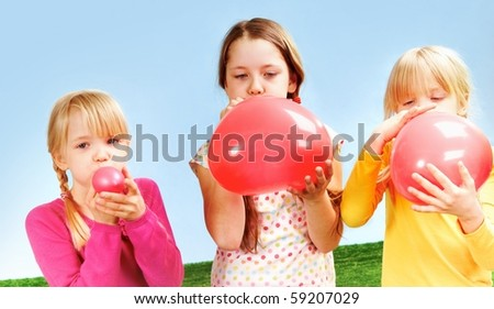 Three girls blowing balloons - stock photo