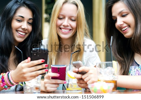 three girls chatting with their smartphones - stock photo