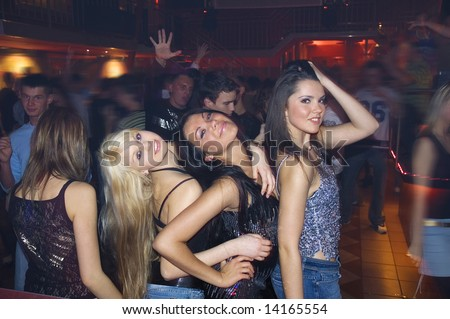 three girls dancing a night in disco with other people - stock photo