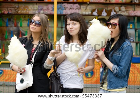 Three girls eating candy floss - stock photo