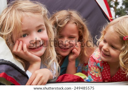 Three Girls Enjoying Camping Holiday On Campsite  - stock photo