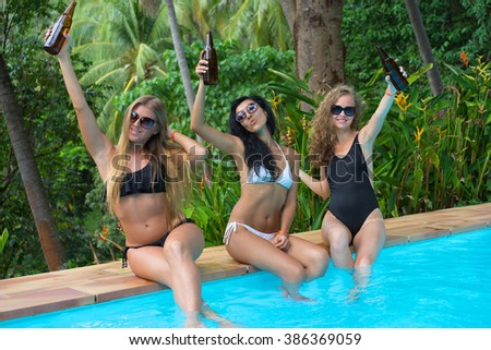 Three girls have party in swimming pool. Vacation concept.  - stock photo