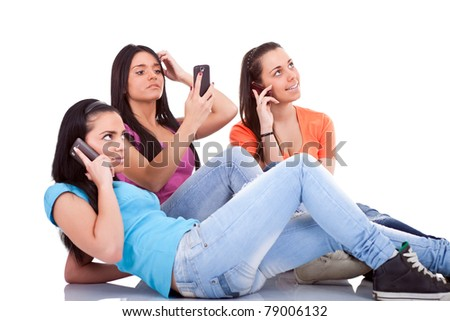 three girls having fun with cell phones, isolated white background - stock photo