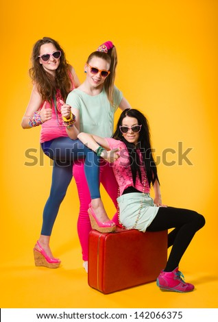 Three girls hitchhike together, red suitcase, yellow background