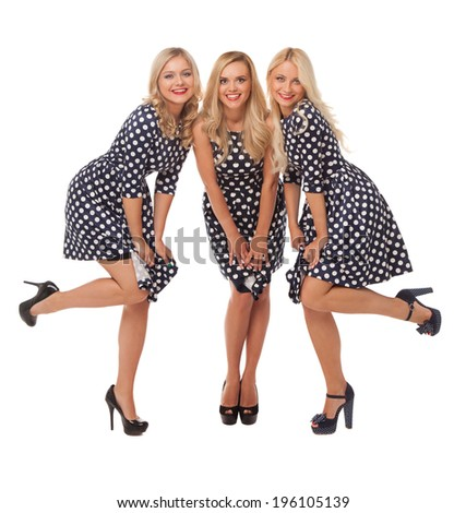 three girls in dot dresses and black shoes over white background  - stock photo